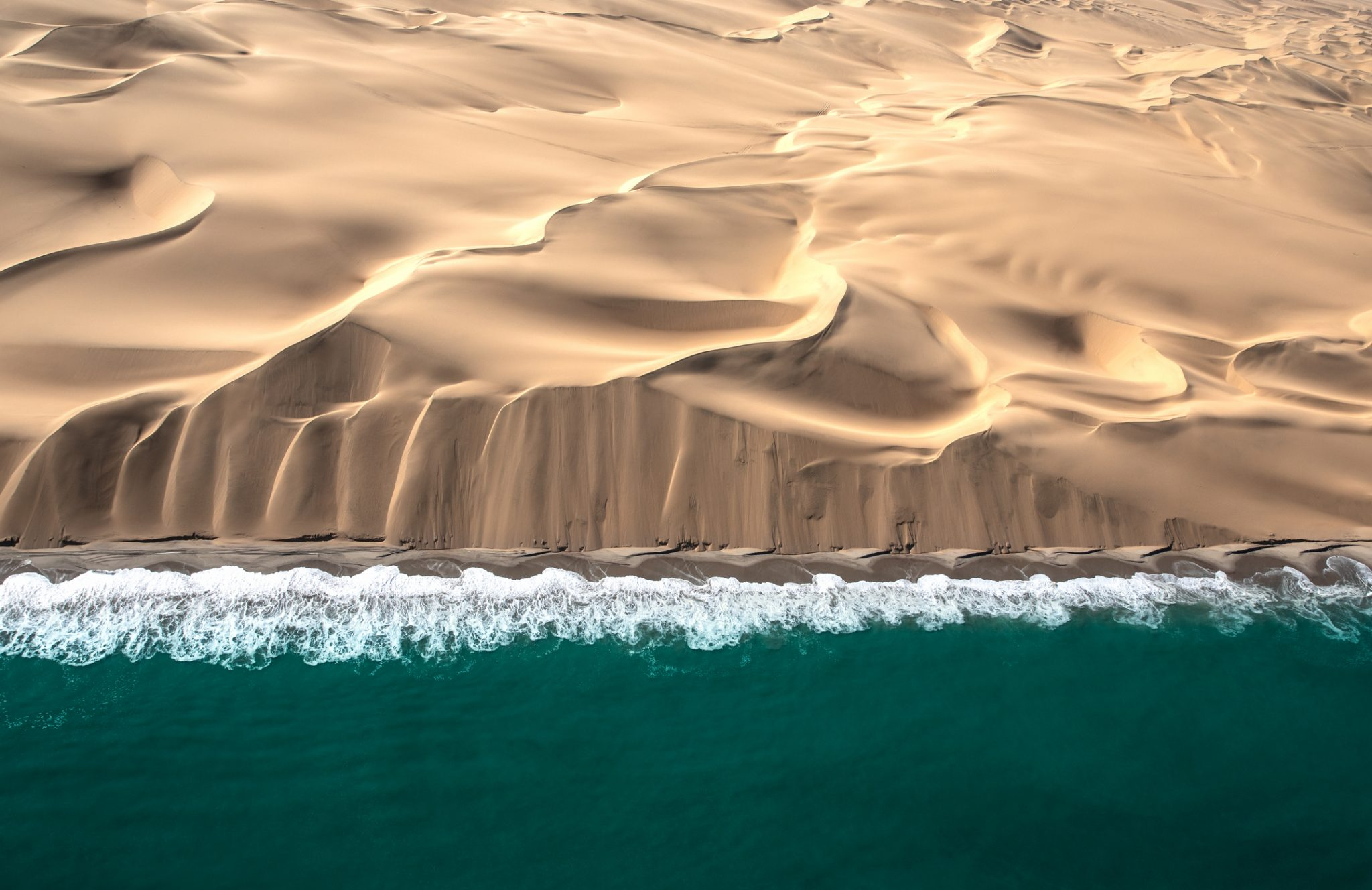 Aerial view of Skeleton coast dunes meeting Atlanic ocean.