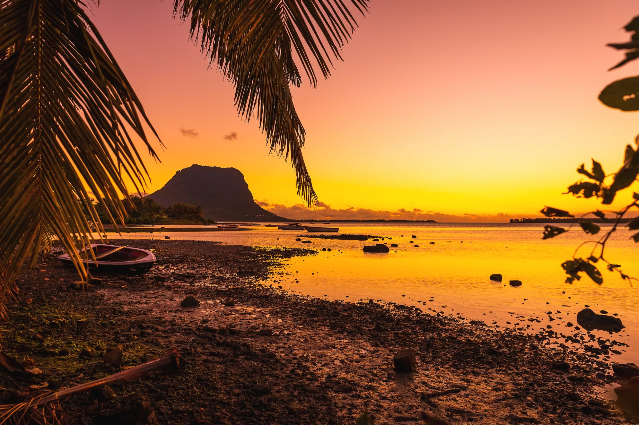 Fishing boats in a quiet ocean at sunset time. Le Morn mountain in Mauritius.